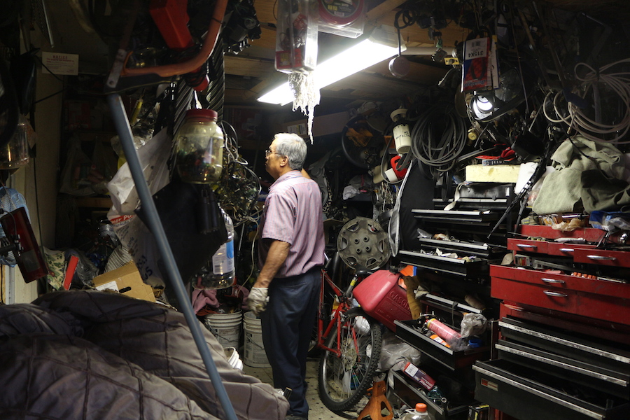 My dad searching through a jungle of tools to fix my car. Can you believe that it's actually our garage? (MONICA CHAN)