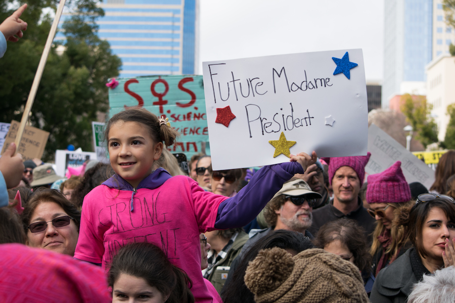 """A young marcher shows another child her """"Future Madame President"""" sign. (BRIAN LANDRY / AGGIE)"""