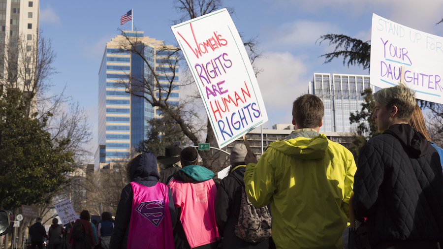 As the marchers marched through the streets, an American flag can be seen in the distance while in the foreground protest signs linger, sending a silent message to Americans. (BRIANA NGO / AGGIE)