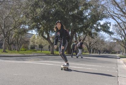 Skateboarders soar smoothly across campus