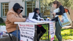 """The cost of living is too damn high!"" Petition circulators outside Shields Library tell their story"