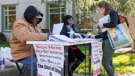 """""""The cost of living is too damn high!"""" Petition circulators outside Shields Library tell their story"""